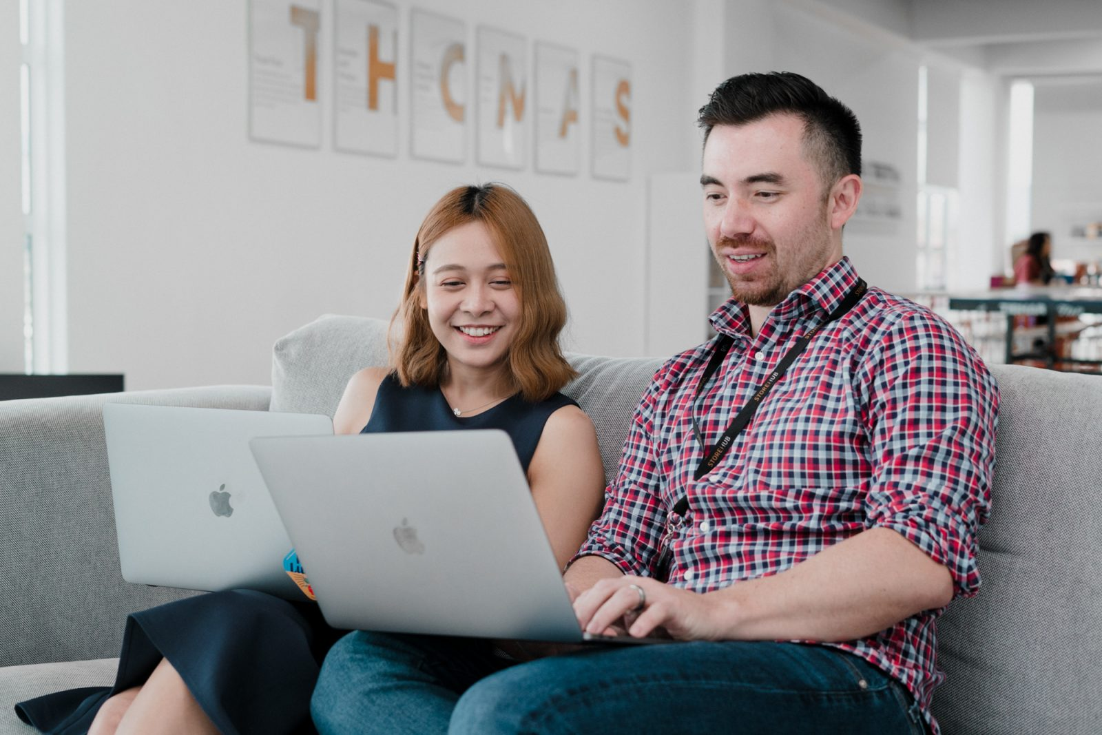 woman and man working on sofa with laptop