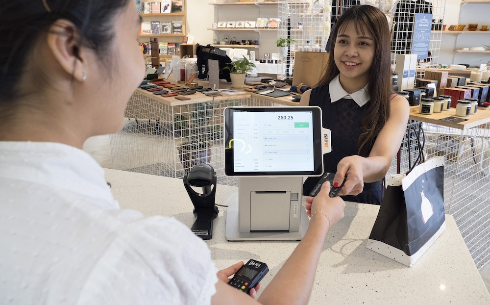 woman paying for item at cash register with credit card